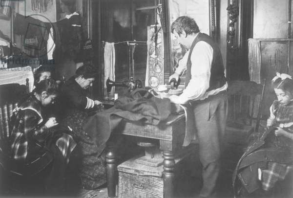 Family working on clothing in a tenement apartment, New York City, USA, c.1906 (b/w photo)