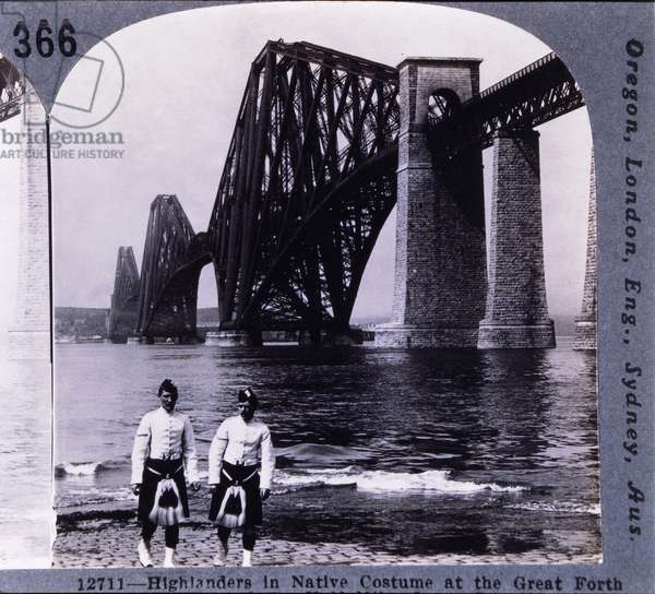 Two Male Highlanders in Native Costume Standing on the Bank of the Firth of Forth Near the Forth Rail Bridge, Queensferry, Scotland, circa 1900