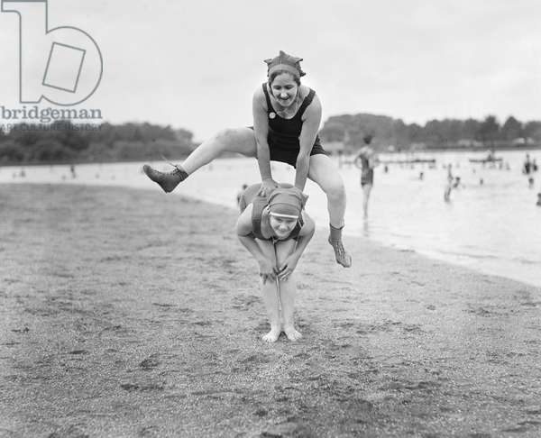 Two Young Women Playing Leap Frog on Beach, USA, 1921 (b/w photo)