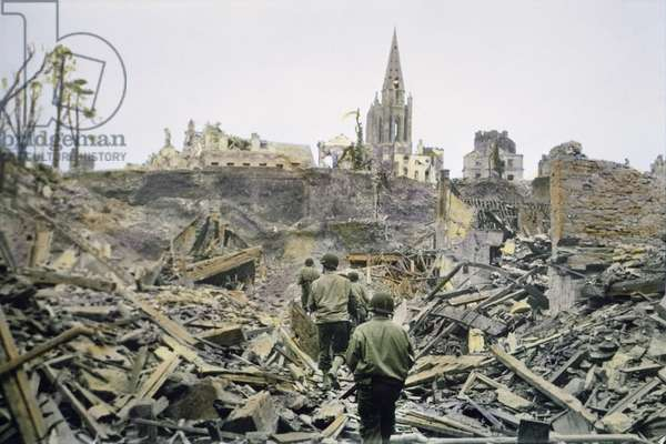 American Infantry Patrol Walking Through Ruins of the French Town, Saint-Lo, after it was Captured from the Germans, South Tower of Church of Notre Dame de Saint-Lo in Background, Battle of Normandy, Saint-Lo, France, July 1944 (photo)