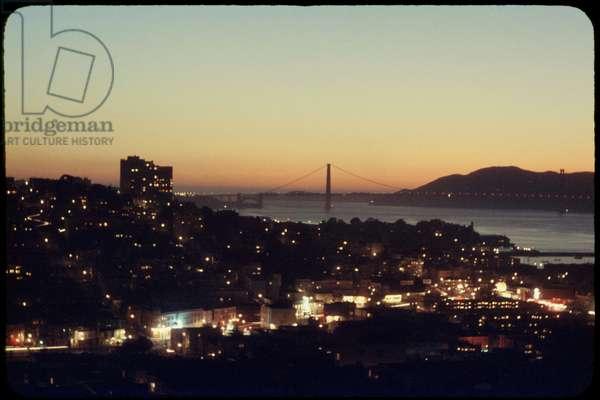 Illuminated Cityscape with Golden Gate Bridge in Background at Sunset, San Francisco, California, USA, 1957