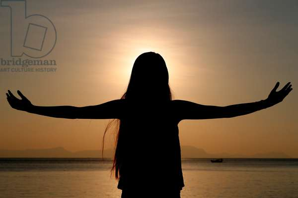 Silhouette of a woman standing by the sea at sunset doing yoga pose and meditation.  Kep.  Cambodia.  (photo)