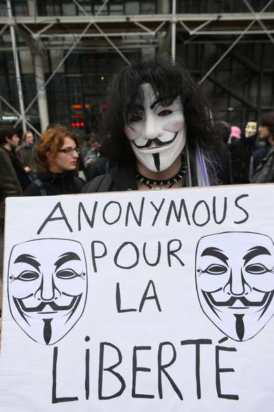 Protester wearing a Guy Fawkes mask , trademark of Anonymous movement and based on character in the film V for Vendetta ; Paris France