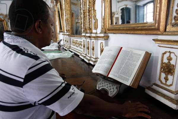 Brazil, Bahia, Salvador : Man reading the Bible in Bonfim churc