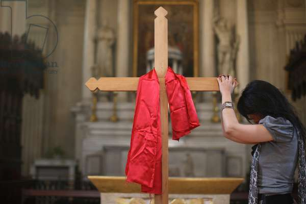 Red fabric on cross on Good Friday. Woman praying. Sallanches France