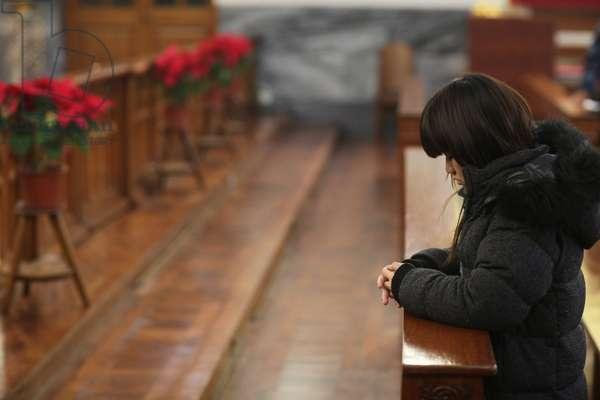 Chinese woman praying in a church. Macau China