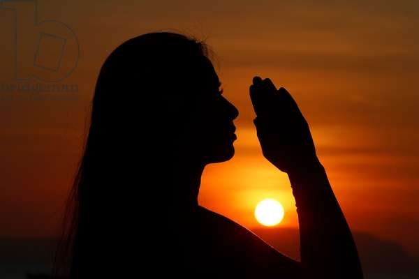 Silhouette of a woman standing by the sea at sunset doing yoga pose and meditation.  (photo)