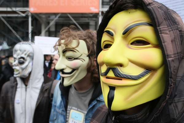 Protesters wearing Guy Fawkes masks , trademark of the Anonymous movement and based on a character in the film V for Vendetta ; Paris France