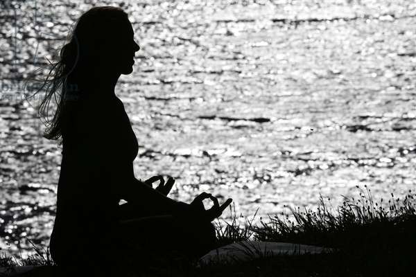 Silhouette of woman practicing yoga at sunset. Lotus position. French Alps. France