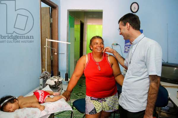 Brazil, Bahia, Salvador : French priest Etienne Kern visiting a parishioner in her workshop in Alagados favel