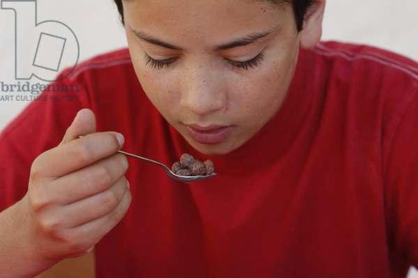 Teenage boy eating breakfast cereals, , Italie