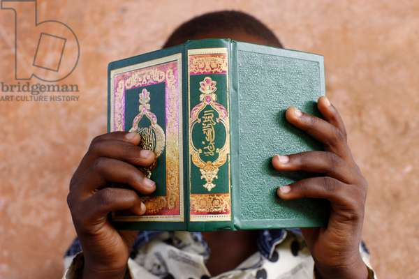 Young african boy reading the Koran, Lome, Togo