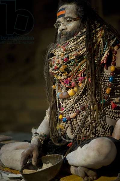 Lali Baba, a priest in Varanasi, waiting for worshipers that he will bless with ash (in the bowl at his feet)He is wearing necklaces given to him to worship Shiva, Varanasi, Inde