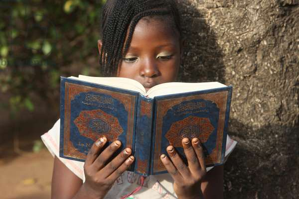 Young girl reading the koran, Lome, Togo