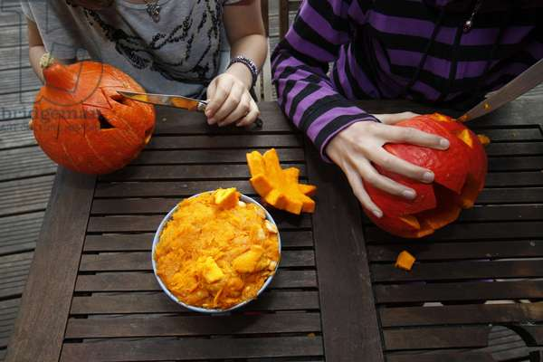 Girls preparing pumpkins for Halloween Sadirac France