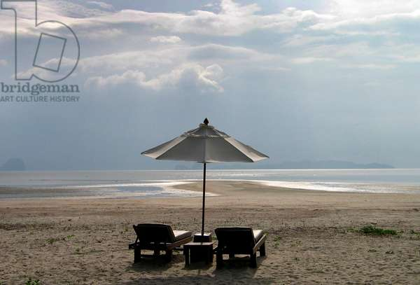 Thai beach with loungers and sunshade.