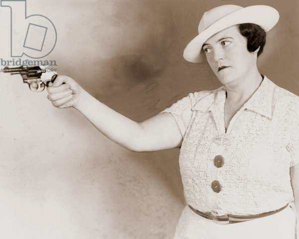 Serious Woman Aiming a Revolver, 1937 (silver print photograph)