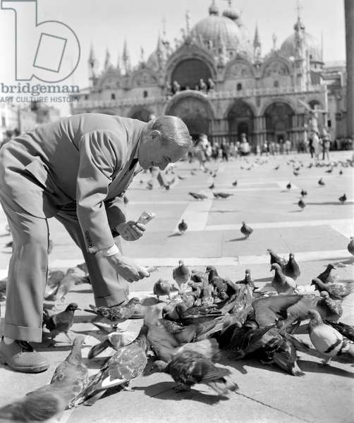 THE PAINTER AND SCULPTOR JOAN MIRO IN S. MARCO SQUARE (St. Marco Square, San Marco). It gives pigeons food - VENICE - 1952