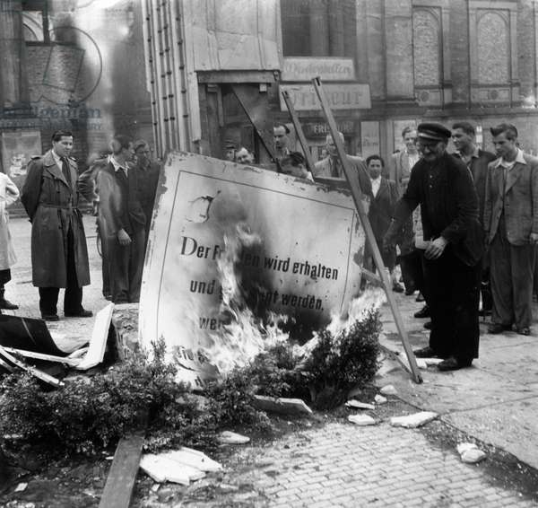 Demonstrators burning a banner, in front of Potsdamer station, Berlin, 17th June 1953 (b/w photo)