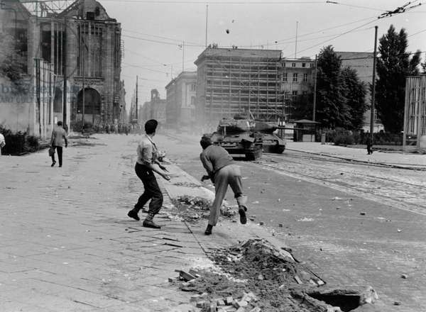 Demonstrators on Leipziger Strasse throwing stones at a passing Soviet tank, Mitte, Berlin, 17th June 1953 (b/w photo)
