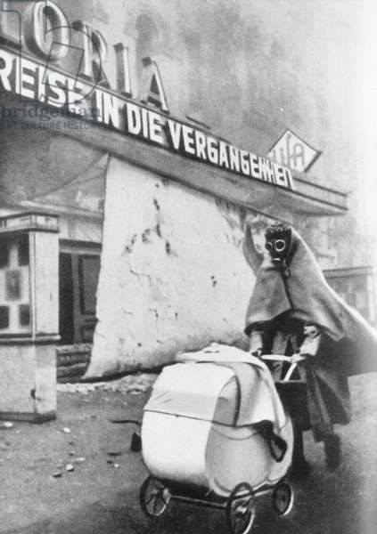 """Woman with """"people's gas mask"""" and pram in front of the Gloria Palast in Berlin during an air raid, c.1944 (b/w photo)"""
