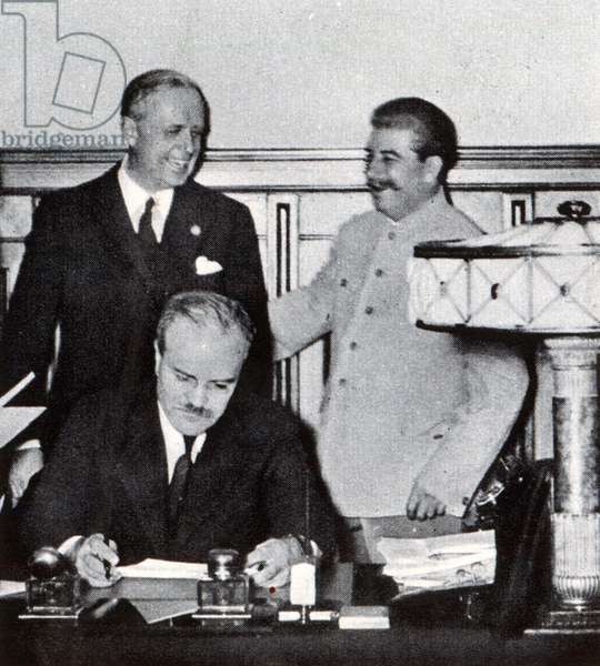 Stalin pats Ribbentrop on the back, while Molotov scans the signed pact which partitioned Poland, from 'The Illustrated War News', published 1st November 1939 (b/w photo)