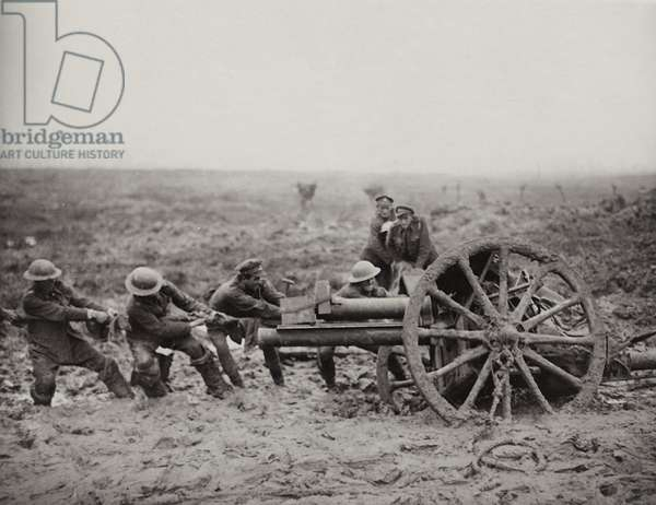 Pulling and jacking a field gun out of the mud to get it in a new position, Flanders, 1914-18 (b/w photo)