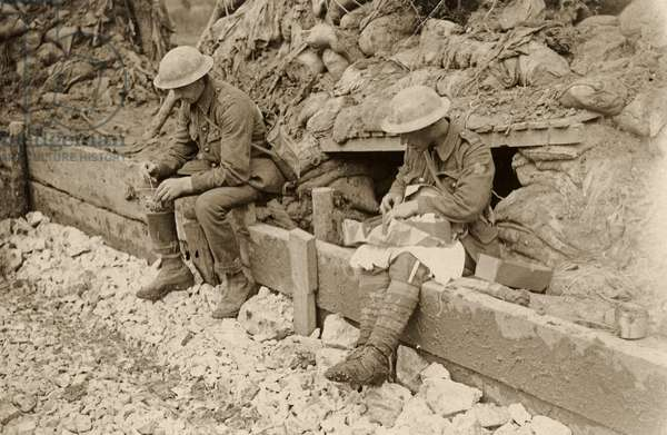 British artilleryman opens a care package from home, Western Front, 1914-18 (b/w photo)
