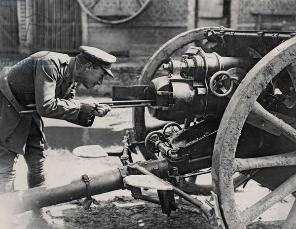 British soldier examines the breech of an artillery piece on the Western Front, 1914-18 (b/w photo)