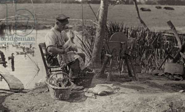 Britihs solder plucking a duck on a Belgian farm during WWI, 1914-18 (b/w photo)