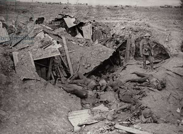 A British soldier stands in a German machine gun emplacement after its destruction by shelling, France, 1914-18 (b/w photo)