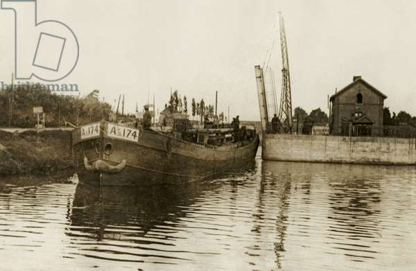 Laden barges passing through a lock during WWI, 1914-18 (b/w photo)