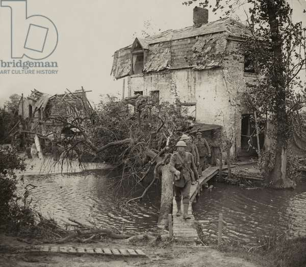 British Tommies leaving their billet in a badly shelled village near Boesinghe, Flanders, 1914-18 (b/w photo)