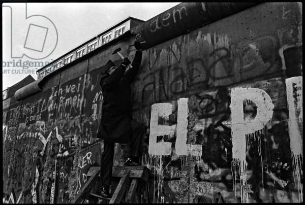 An American Officer of the Berlin Brigade uses a hammer and chisel to take a piece of the Berlin Wall near Checkpoint Charlie, 23rd November 1989 (b/w photo)