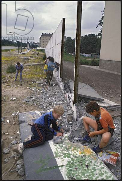Children playing, dismantling pieces of the Berlin wall in the former military zone, Bernauer Strasse, Wedding, June 1990 (photo)