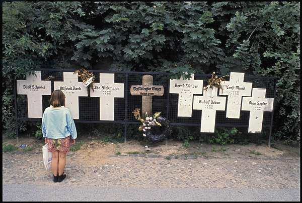 Child observing commemorative crosses for casualties of the Berlin Wall, Bernauerstrasse, Wedding, July 1990 (photo)