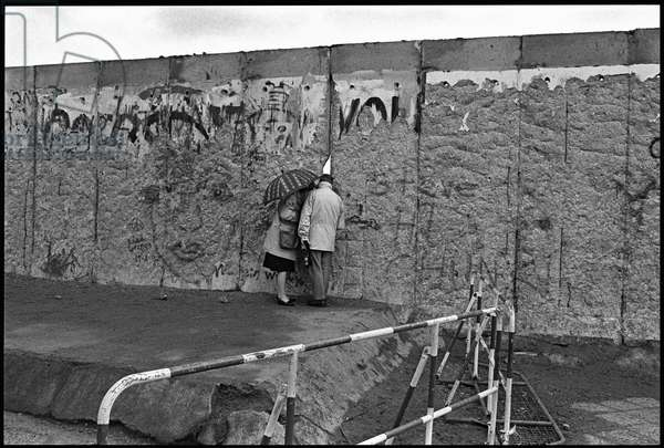 East Berliners peer through a gap in the Berlin Wall made by the so-called 'Wall Woodpeckers', 10th March 1990 (b/w photo)