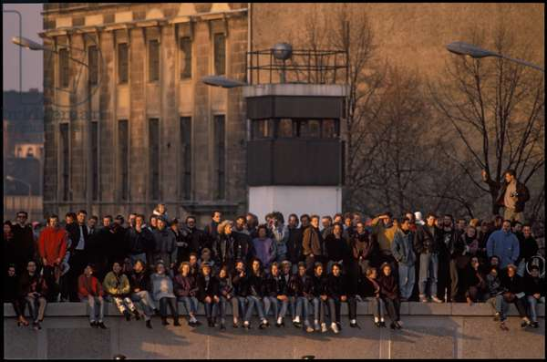 Crowd seated on top of the Berlin Wall, whilst GDR border controllers wait below, in the area in front of the Brandenburg Gate and Pariser Platz, Berlin, East Germany, 10th November 1989 (photo)
