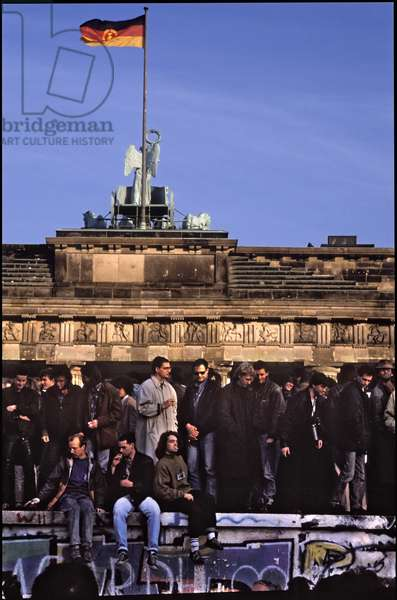 Berliners from East and West celebrating the opening of the border standing on the Berlin Wall, Brandenburg Gate, Berlin, 9th November 1989 (photo)
