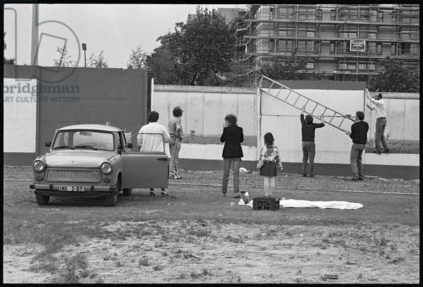 Visitors to the the former military zone at Bernauer Strasse, observing the Berlin Wall, Wedding, Berlin, June 1990 (b/w photo)