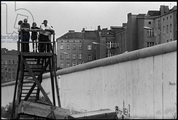 Visitors on a viewing platform at the barricades in front of the Berlin Wall, 1981 (b/w photo)