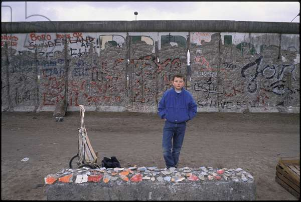 A young boy sells pieces of the Berlin Wall, Potsdam Square, Berlin, 10th March 1990 (photo)