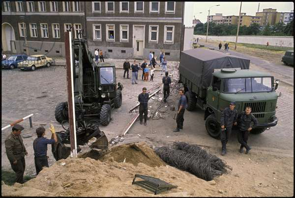 Tourists collecting souvenirs from an ex-military zone as military engineers dismantle a border crossing, Bernauer Strass, Wedding, Berlin, June 1990 (photo)