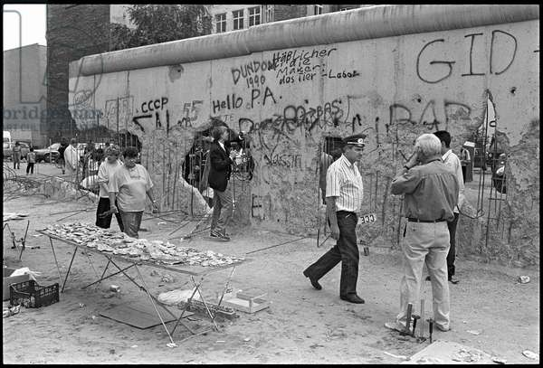 Vendors selling pieces of the Berlin Wall to sell to tourists, at the former border crossing, Checkpoint Charlie, Kreuzberg, Berlin, July 1990 (b/w photo)