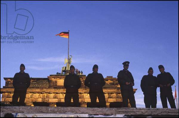 Soldiers on top of the Berlin Wall, in front of the Brandenburg Gate, Berlin, East Germany, 10th November 1989 (photo)