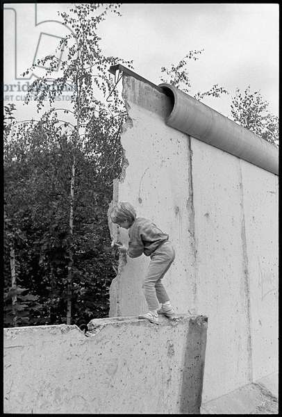 Child playing, dismantling pieces of the Berlin wall in the former military zone, Bernauer Strasse, Wedding, June 1990 (photo)