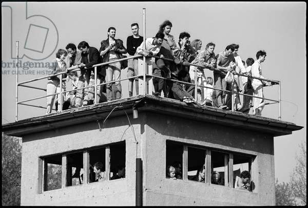 Berliners standing on an abandened police watchtower, after the fall of the Berlin Wall, Schwedter Strasse, Bezirk, Prenzlauer Berg, April 1990 (b/w photo)