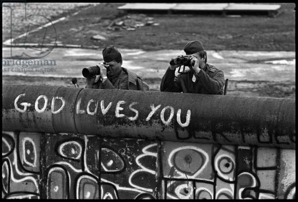 East German border guards watch protestors in the Lenne-Dreiecks area, 1988 (b/w photo)