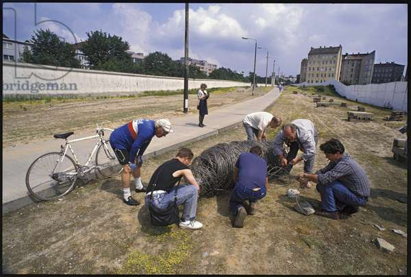 Residents and tourists taking souvenirs from the former military zone adjacent to the Berlin Wall, Bernauer Strasse, Wedding, June 1990 (photo)