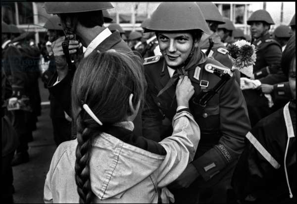 Girl giving a soldier a gift after the Military Parade of the National People's Army to celebrate the 32nd anniversary of the founding of East Germany, 1981 (b/w photo)